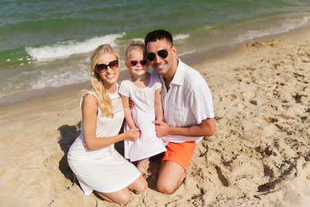 happy life: family, vacation, adoption and people concept - happy man, woman and little girl in sunglasses on summer beach