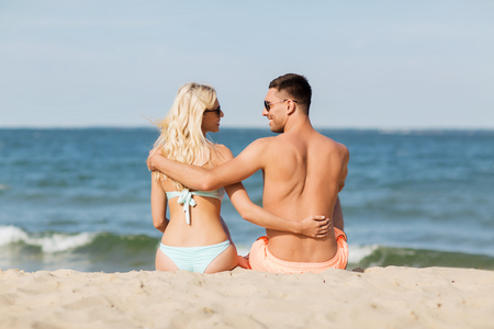 fling: love, travel, tourism, summer and people concept - smiling couple on vacation in swimwear sitting and hugging on beach from back