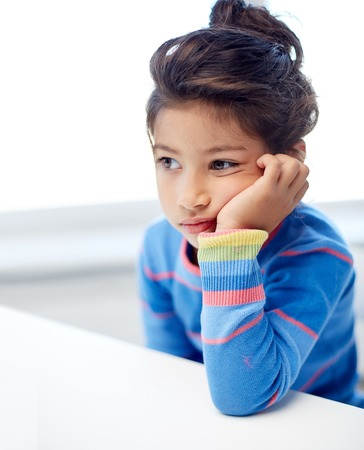 people, childhood and emotions concept - sad or bored little girl at home, kindergarten or school Stock Photo