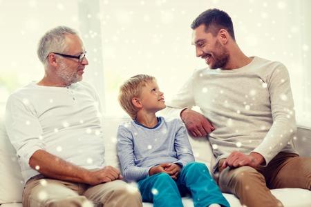 niños sentados: familia, la felicidad, el concepto de generación y la gente - sonriente padre, hijo y abuelo sentado en el sofá en casa