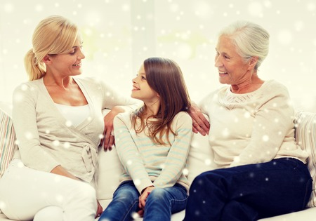 grandmother mother daughter: family, happiness, generation and people concept - smiling mother, daughter and grandmother sitting on couch at home