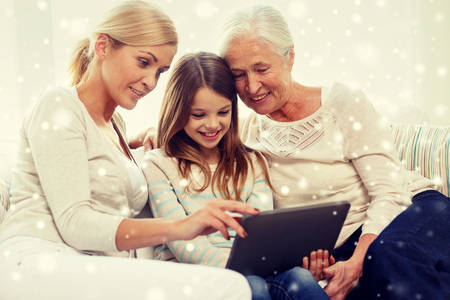 computer generation: family, generation, technology and people concept - smiling mother, daughter and grandmother with tablet pc computer sitting on couch at home