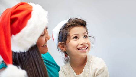 asian preteen: christmas, holidays, family, childhood and people concept - happy mother and little girl in santa hats at home