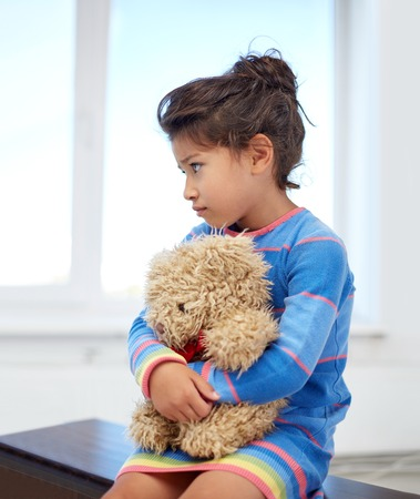 petite fille triste: l'enfance, la tristesse, la solitude et les gens concept - petite fille triste avec ours en peluche jouet � la maison Banque d'images