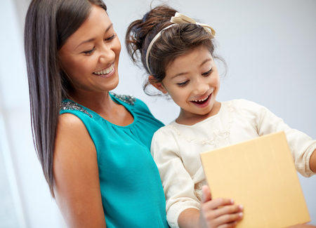 holidays, birthday family, childhood and people concept - happy mother and little girl with gift box at home