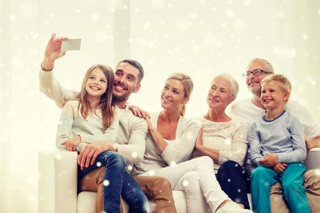 家庭: 家庭,技術,生成和人的概念 - 幸福的家庭坐在沙發上,在家自製自拍照用智能手機