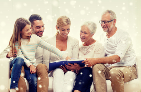 mature old generation: family, happiness, generation and people concept - happy family with book or photo album sitting on couch at home Stock Photo