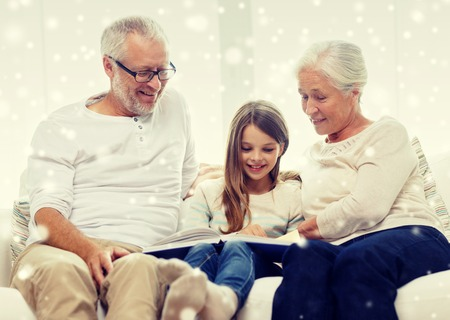 generation: family, generation, education and people concept - smiling grandfather, granddaughter and grandmother with book or photo album sitting on couch at home