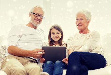 computer generation: family, generation, technology and people concept - smiling grandfather, granddaughter and grandmother with tablet pc computer sitting on couch at home