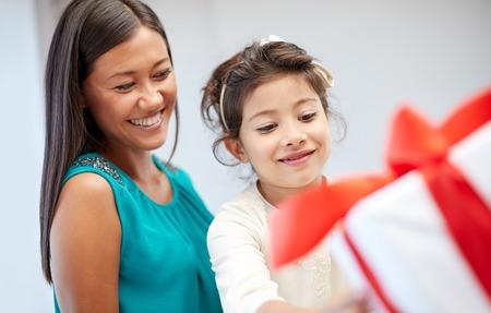 madre soltera: días de fiesta, cumpleaños de la familia, la infancia y las personas concepto - Madre y niña felices con caja de regalo en el país Foto de archivo