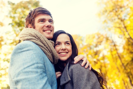 relationship: love, relationship, family and people concept - smiling couple hugging in autumn park Stock Photo