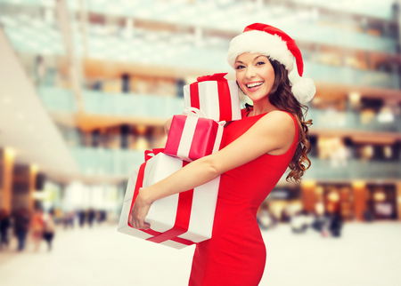 nice girl: christmas, holidays, celebration and people concept - smiling woman in red dress with gift boxes over shopping center background