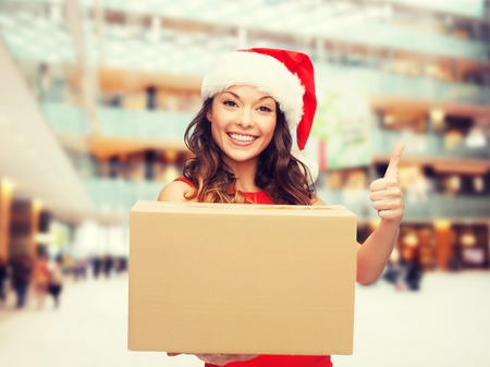 delivery box: christmas, winter holidays, delivery, gesture and people concept - smiling woman in santa helper hat with parcel box showing thumbs up over shopping center background Stock Photo