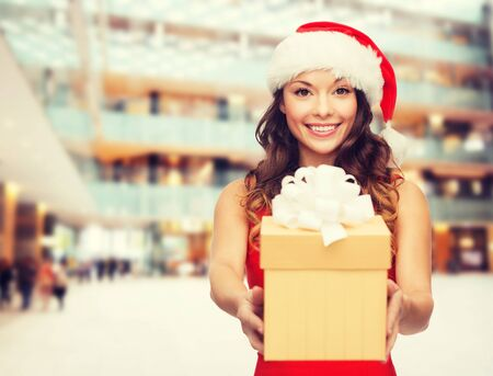 christmas present: christmas, holidays, celebration and people concept - smiling woman in red dress with gift box over shopping center background