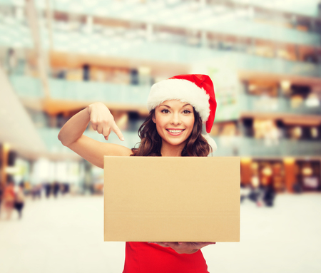 delivery box: christmas, winter, holidays, delivery and people concept - smiling woman in santa helper hat with parcel box over shopping center background