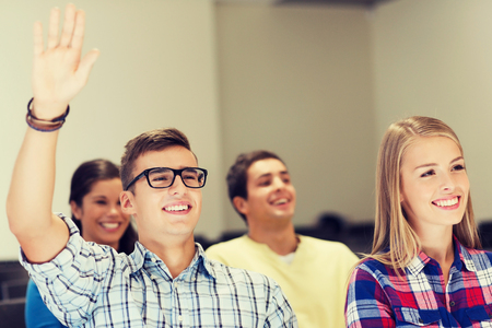 questions: education, high school, teamwork and people concept - group of smiling students raising hand in lecture hall