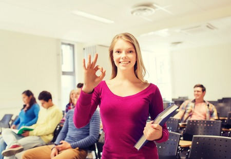good looking teenage guy: education, high school, teamwork and people concept - group of smiling students with notepads showing ok gesture in lecture hall