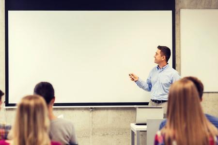 교육, 고등학교, 기술과 사람들 개념 - 교실에서 원격 제어와 함께 서있는 교사, 화이트 보드 앞에 노트북 컴퓨터와 웃는 학생 스톡 콘텐츠