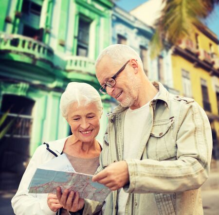 tourists: family, age, tourism, travel and people concept - senior couple with map over latin american city street background