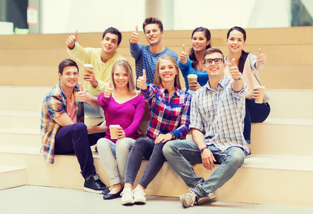 university students: education, high school, friendship, drinks and people concept - group of smiling students with paper coffee cups showing thumbs up gesture Stock Photo