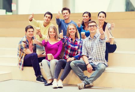 estudiantes universitarios: la educación, la escuela secundaria, la amistad, las bebidas y la gente concepto - grupo de estudiantes sonrientes con las tazas de café de papel que muestra los pulgares para arriba gesto