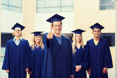 graduate: education, graduation, gesture and people concept - group of smiling students in mortarboards and gowns showing thumbs up outdoors