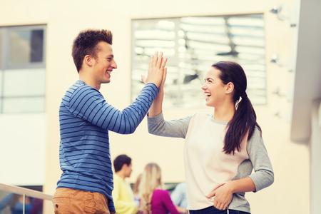 nene y nena: amistad, el gesto, la educación y concepto de la gente - grupo de estudiantes sonrientes al aire libre haciendo chocar los cinco