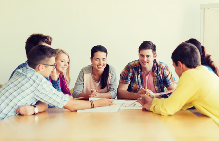 deciding: education, school, architecture and people concept - group of smiling students with blueprint meeting indoors Stock Photo