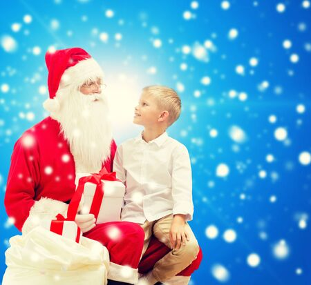 with bag: holidays, christmas, childhood and people concept - smiling little boy with santa claus and gifts over blue snowy background