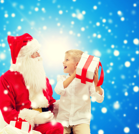 little boys: holidays, christmas, childhood and people concept - smiling little boy with santa claus and gifts over blue snowy background