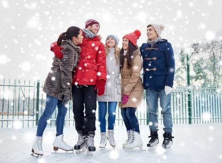 niño en patines: gente, invierno, la amistad, el deporte y el ocio concepto - amigos felices de patinaje sobre hielo y abrazos en pista al aire libre Foto de archivo