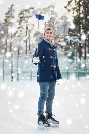 winter clothing: people, winter, technology and leisure concept - happy young man taking picture with smartphone selfie stick on ice skating rink outdoors