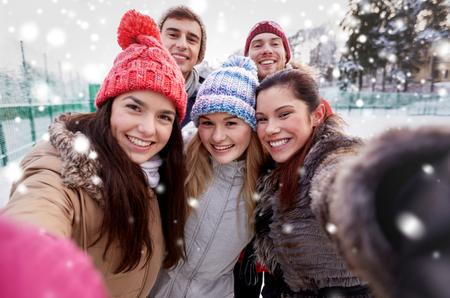 ropa invierno: la gente, la amistad, la tecnolog�a, el invierno y concepto de ocio - amigos felices que toman Autofoto con el tel�fono inteligente o una c�mara al aire libre