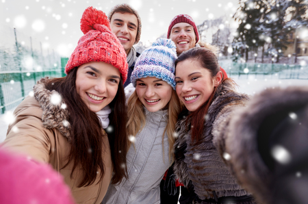 winter season: people, friendship, technology, winter and leisure concept - happy friends taking selfie with smartphone or camera outdoors