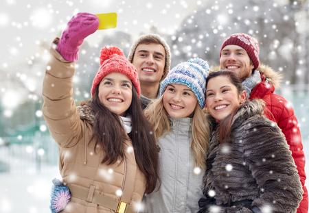 pareja adolescente: la gente, la amistad, la tecnolog�a, el invierno y concepto de ocio - amigos felices que toman Autofoto con el tel�fono inteligente al aire libre Foto de archivo
