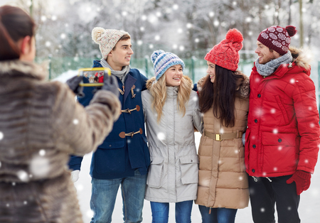 group picture: people, friendship, winter, technology and leisure concept - happy friends taking picture with smartphone outdoors