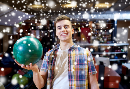 entertainment concept: people, leisure, sport and entertainment concept - happy young man holding ball in bowling club at winter season