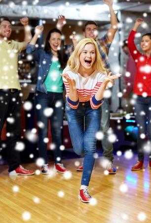 bolos: la gente, el ocio, el deporte y el concepto de entretenimiento - mujer joven feliz que lanza la bola en club de bolos en la temporada de invierno Foto de archivo