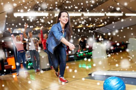 사람들, 레저, 스포츠 및 엔터테인먼트 개념 - 겨울에 볼링 클럽에서 공을 던지고 행복 한 젊은 여자