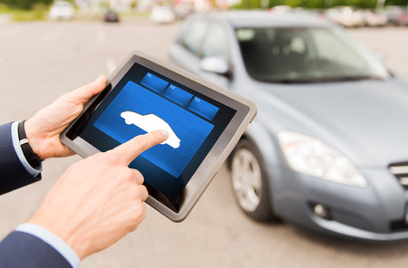 car parking: transport, business trip, technology and people concept - close up of male hands with car icon tablet pc computer screen outdoors Stock Photo
