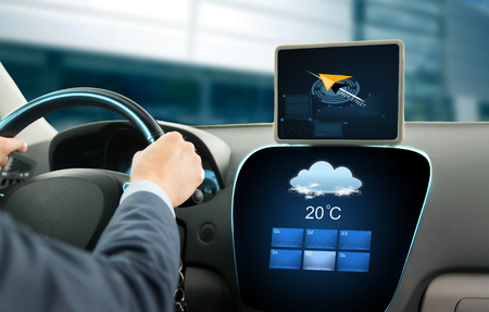 driving a car: transport, business trip, technology and people concept - close up of businessman driving car with navigator on tablet pc and on board computer showing weather forecast