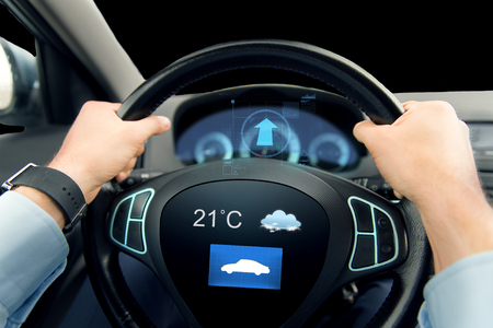 sensor: transport, business trip, technology and people concept - close up of male hands holding car wheel and driving with weather sensor on board computer screen Stock Photo