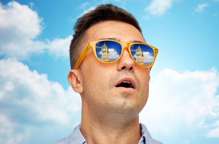big mouth: travel, tourism, sightseeing, emotions and people concept - face of man in sunglasses looking at big ben tower over blue sky and clouds background