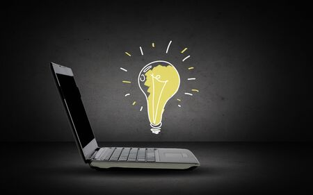 idea bulb: technology, business, start up and idea concept - open laptop computer with lighting bulb doodle over dark gray background