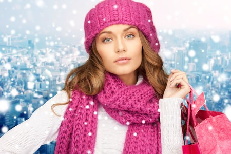 christmas shopping bag: holidays, christmas, sale and people concept - young woman in winter clothes with shopping bags over snowy city background