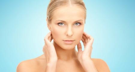 schoonheid, mensen en gezondheidszorg concept - mooie jonge vrouw aan te raken haar nek over blauwe achtergrond Stockfoto