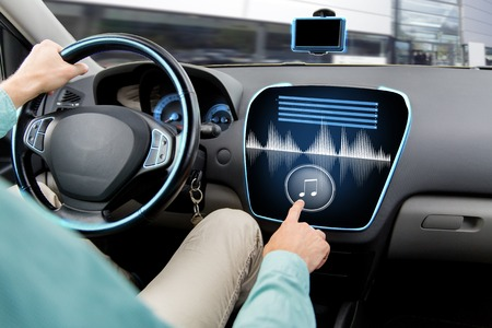 transport, modern technology, music and people concept - close up of man driving car with audio stereo system on board computer