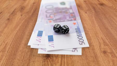 dinero euros: casino, juegos de azar y la fortuna concepto - cerca de dados negros y dinero efectivo en euros en el fondo mesa de madera Foto de archivo
