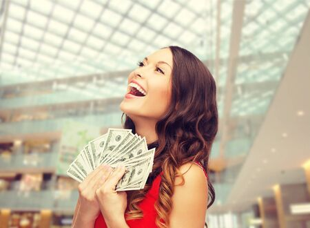 red centre: christmas, x-mas, shopping, banking and people concept - smiling woman in red dress with us dollar money over shopping centre background Stock Photo