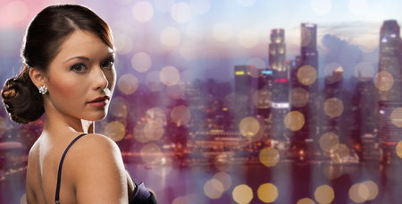 people, holidays, jewelry and luxury concept - woman face with diamond earring over night singapore city and lights background Stock Photo